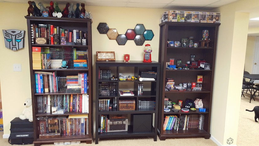 2 tall, wide bookcases flank a shorter shelf that has cube shelving. The right bookcase houses gamebooks and RPG books. The left bookcase houses dice, games with tin boxes, and other small gaming related trinkets. The central shelf houses gaming books, small chests with games inside, and the Invisible Sun Black Cube. Above the central shelf is a metal art piece (a series of hexagons in dark colors).