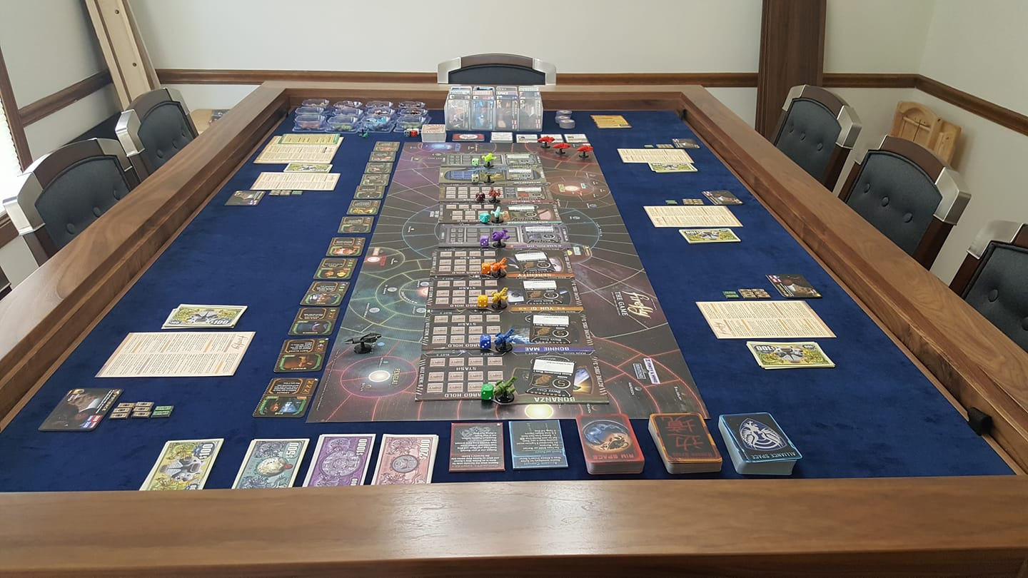 The cover leaves have been removed from the table to reveal the inner vault area. All of the components for the Firefly game are setup inside the vault, including all expansions and the game mat.