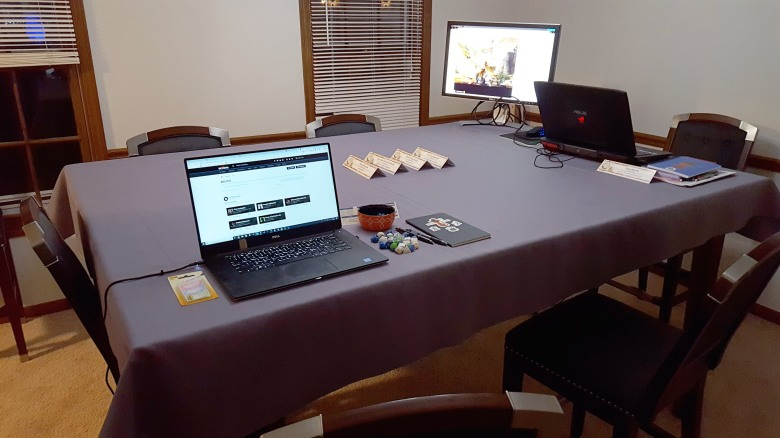 The table is covered with a table cloth. The Dungeon Master area is set up at one end with a computer monitor, laptop, and books. One player area is also setup with a laptop, books, dice, etc.